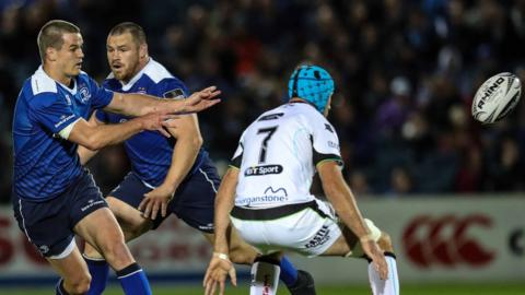 Leinster's Johnny Sexton passes as Ospreys Justin Tipuric holds the defensive line