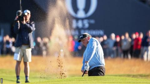 Colin Montgomerie hits the ball out the bunker on the first hole
