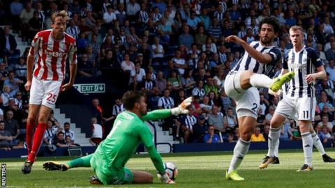 Ahmed Hegazi (right) and Ben Foster (centre) fail to clear
