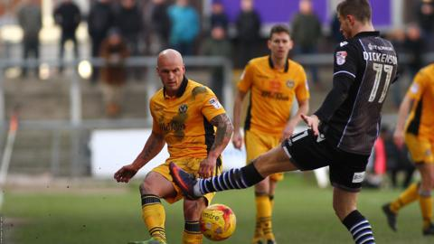 Action shot from Newport v Colchester, two players challenge for the ball