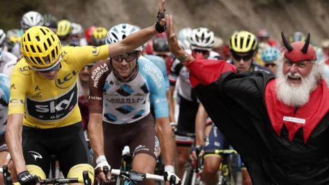 Chris Froome high fives the Tour Devil