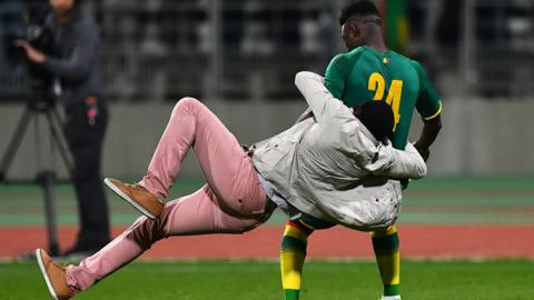 An Ivory Coast players is rugby tackled by a fan