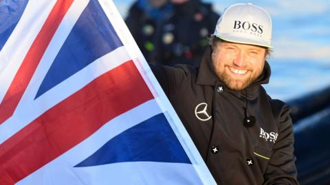 Alex Thomson waves the Union Flag after completing the Vendee Globe round the word yacht race
