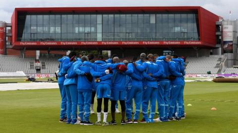 West Indies in a huddle after the delayed start