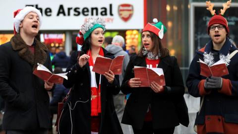 Carol singers ahead of the match