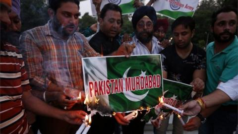 "Members of National Human Rights and Crime Control Organization burn posters of the Pakistan flag with the slogan ""Pakistan Murdabad"" (""Down with Pakistan"") printed on them, as they pay tribute to Indian Army soldiers who lost their lives in an attack on an Indian army camp in Uri, in Amritsar, India,"