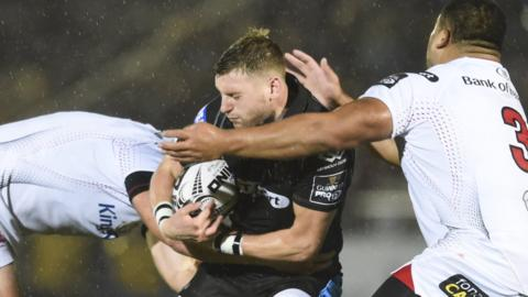 Glasgow fly-half Finn Russell is tackled by two Ulster players