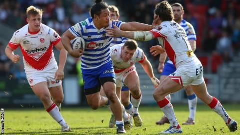 Taulima Tautai of Wigan Warriors holds off a challenge from Louie McCarthy-Scarsbrook of St Helens