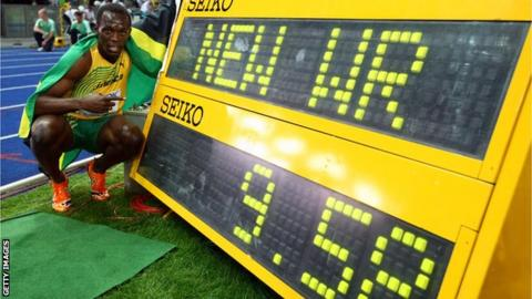 Usain Bolts poses next to the scoreboard showing his 100m world record