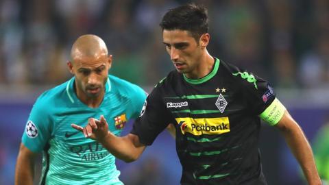 Gladbach captain Lars Stindl shields the ball from Barca's Javier Mascherano