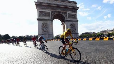 Tour de France riders racing past the Arc de Triomphe in Paris