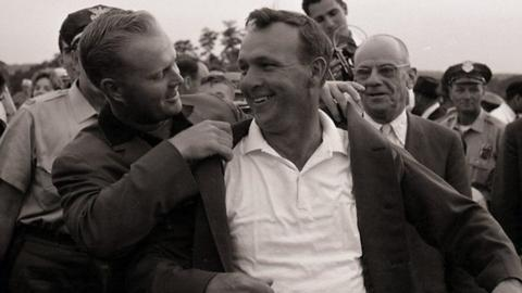 Arnold Palmer receives the green jacket from Jack Nicklaus