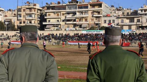 Soldiers watch a football match in Syria