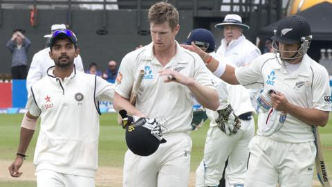 New Zealand's Jimmy Neesham is congratulated by team-mate Neil Wagner and India's Mohammed Shami
