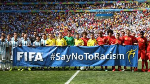 Argentina and Belgium players and referees pose with a banner before a World Cup game in 2014