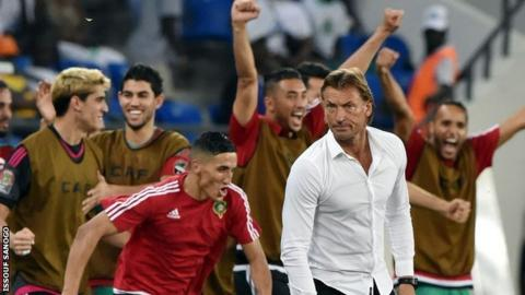 Morocco players celebrate behind coach Herve Renard