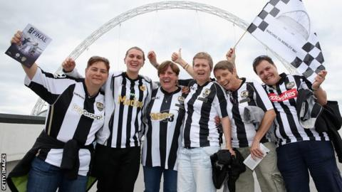 Notts County fans posing in front of Wembley Stadium