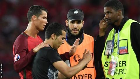 Cristiano Ronaldo of Portugal with a pitch invader during Euro 2016
