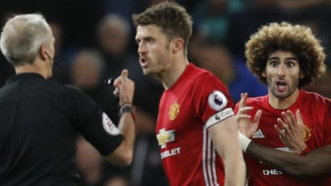 Marouane Fellaini (right) is sent off by referee Martin Atkinson