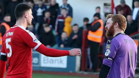 Cliftonville's Johnny Flynn asks for the goalkeeping gloves from Conor Devlin after the Reds number one was sent off during the cup quarter-final