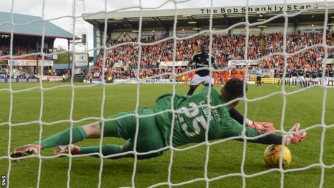 Harry Lewis saves Roarie Deacon's penalty