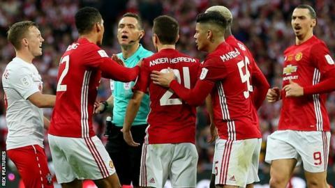 Man Utd players surround the referee