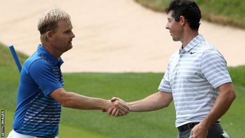 Soren Kjeldsen (L) of Denmark shakes hands with Rory McIlroy