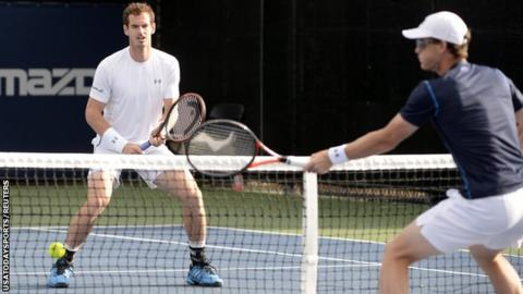 Andy Murray (left) looks on as brother Jamie plays a volley on Montreal