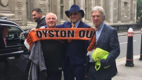 "Owen Oyston (centre) poses outside the court with a protestor holding an ""Oyston Out"" Blackpool scarf"