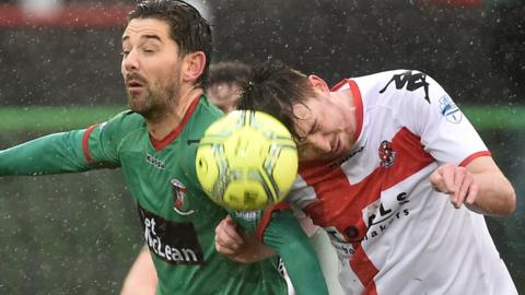 Glentoran's Curtis Allen in action against Billy Joe Burns of Crusaders