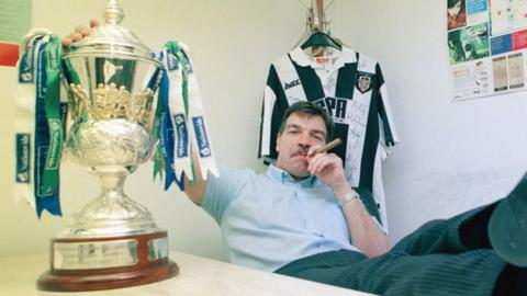 Sam smoking a cigar next to the trophy for winning Division Three