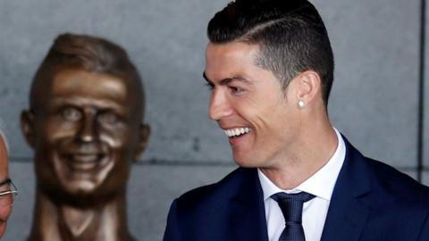 Cristiano Ronaldo se tient devant la statue de lui-même à l'aéroport de Funchal,