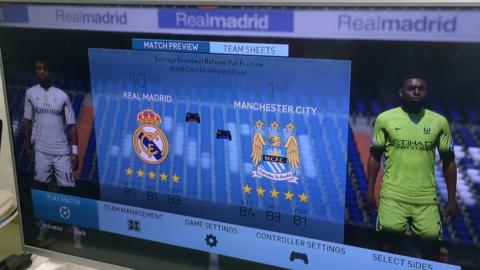 A photo of a TV screen showing a FIFA computer game between Man City and Real Madrid