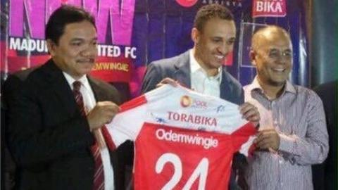 Peter Odemwingie holds up his Madura United shirt