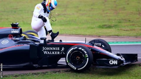 Fernando Alonso steps out of his car after retiring in the Brazilian Grand Prix