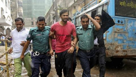 Bangladeshi cricketer Shahadat Hossain is taken away by policemen after he surrendered before a court in Dhaka, Bangladesh
