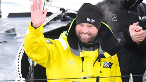 Alex Thomson waves to the crowd after completing the Vendee Globe yacht race