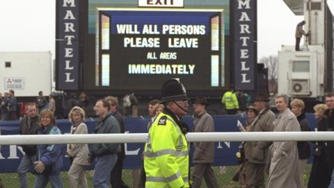 A sign instructs the public on the evacuation procedure due to the IRA bomb scare which postponed The Grand National
