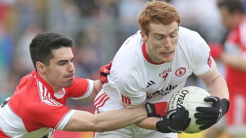 Derry defender Niall Kenan tackles Tyrone's Peter Harte