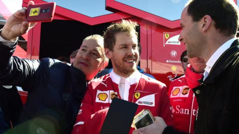 Sebastian Vettel (centre) signs autographs at the Circuit de Catalunya