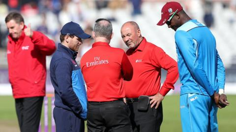 The umpires and captains confer