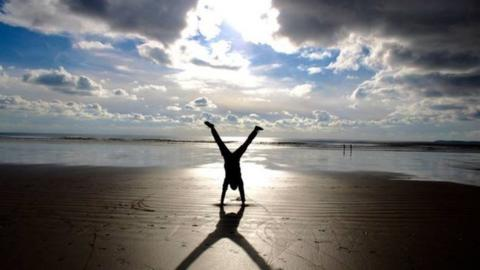 silhouette of someone handstanding on the beach