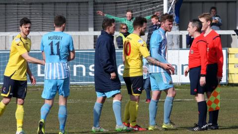 Warrenpoint Town players protest to referee Ross Dunlop after conceding the penalty which sealed their relegation