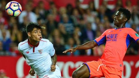 Sevilla's Joaquin Correa (left) heads the ball past Granada's Martin Hongla