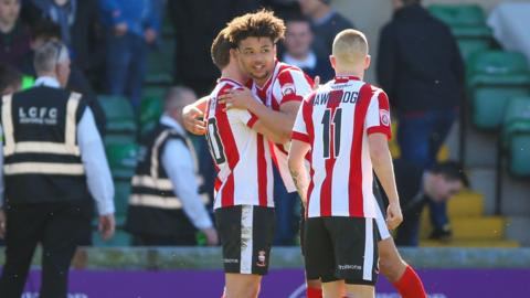 Lincoln players congratulate Lee Angol following his equaliser against Forest Green