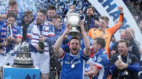 Linfield captain Jamie Mulgrew lifts the Gibson Cup after the Premiership title was secured