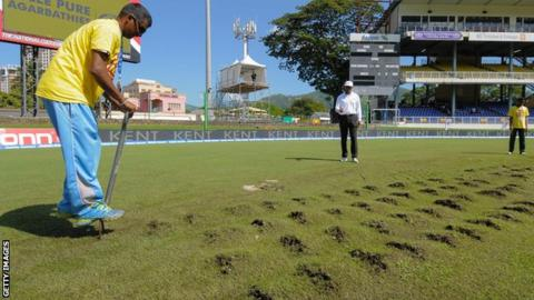 A member of the groundstaff attempts to repair the damaged pitch at Port of Spain