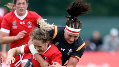 Amy Evans and Rachel Taylor of Wales tackle Canada's Lori Josephson