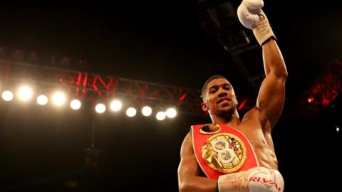 Anthony Joshua raises his arm aloft after a win