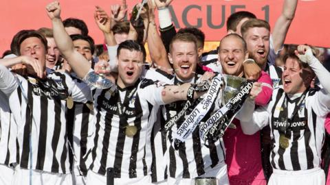 Dunfermline Athletic players celebrate with the Scottish League One trophy